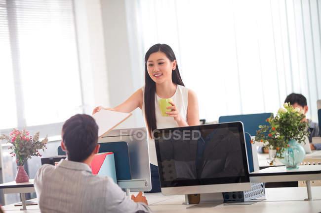 Улыбающаяся молодая деловая женщина, держащая кубок и давая планшет коллеге-мужчине в офисе — стоковое фото