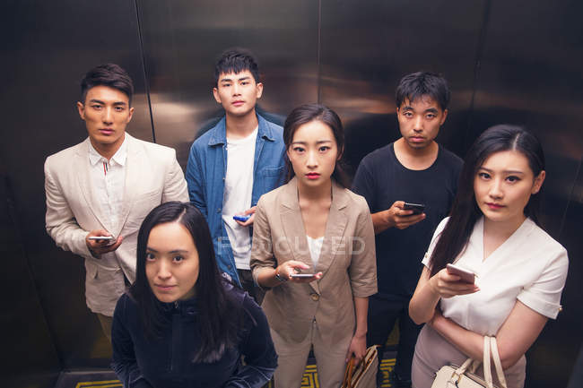 High angle view of serious young asian people holding smartphones and looking at camera in elevator — Stock Photo