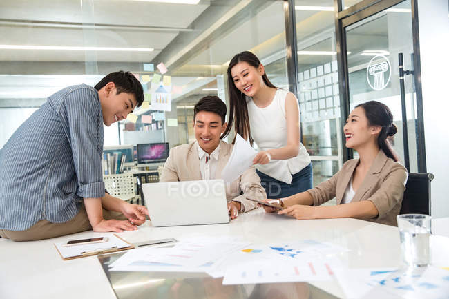 Smiling young asian business people using laptop and working with papers in modern office — Stock Photo