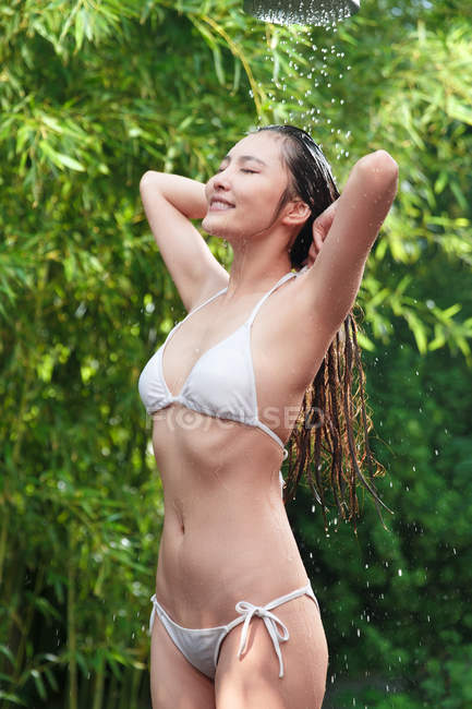 Attractive happy young asian woman in bikini taking shower with closed eyes — Stock Photo