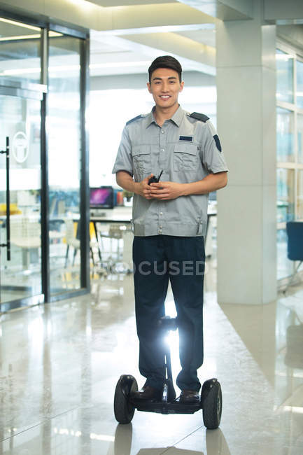 Smiling young asian security guard riding self-balancing scooter and using walkie-talkie in office — Stock Photo