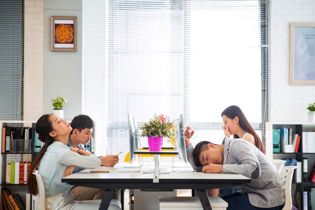Side view of tired young coworkers yawning and sleeping at desk in office — Stock Photo