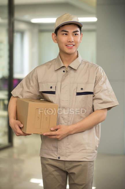 Красивый улыбающийся молодой азиатский курьер, держащий картонную коробку в офисе — стоковое фото