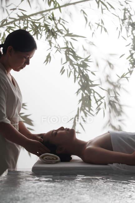 Вид сбоку на молодую расслабленную азиатку, получающую массаж головы в спа — стоковое фото