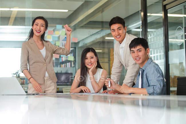 Счастливая молодая азиатская бизнес-команда, работающая вместе и улыбающаяся на камеру в офисе — стоковое фото
