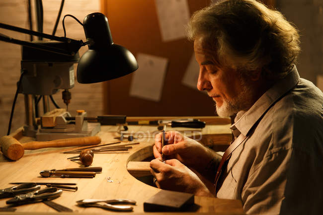 Side view of concentrated mature jewelry designer working with tools in workshop — Foto stock