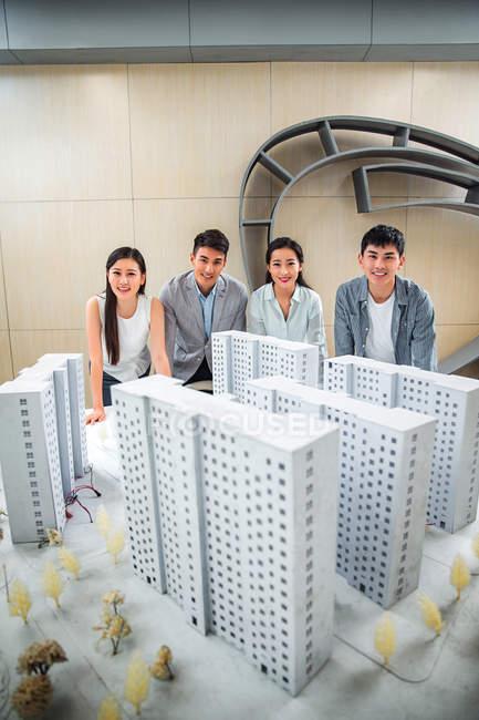 Высокий угол обзора профессиональных молодых азиатских архитекторов, стоящих рядом с моделями зданий и улыбающихся перед камерой в офисе — стоковое фото