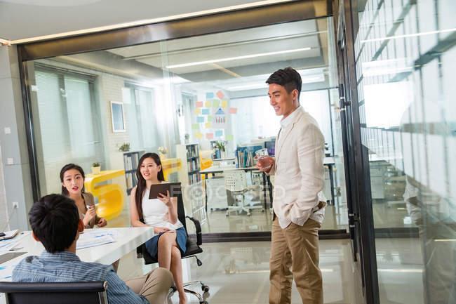 Профессиональные молодые деловые люди обсуждают новый проект в современном офисе — стоковое фото