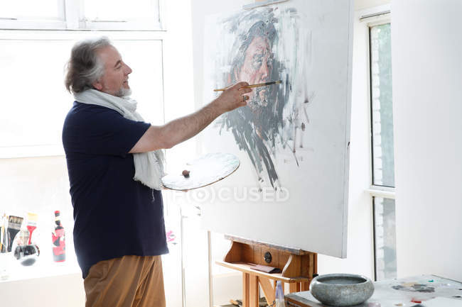 Side view of smiling mature artist painting self-portrait on easel in studio — Stock Photo