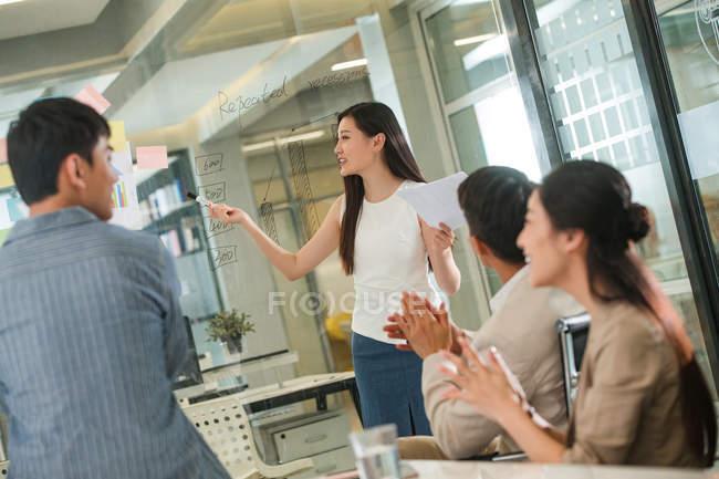 Jeune femme d'affaires de sourire retenant des papiers et pointant sur des notes sur le verre pendant la présentation, des collègues applaudissant au premier plan — Photo de stock