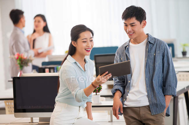 Smiling young asian businessman and businesswoman using digital tablet together in modern office — Stock Photo