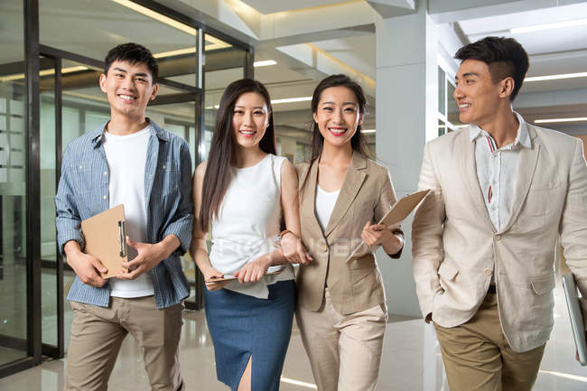 Happy young professional asian business people holding clipboards and smiling at camera while walking together in office — Stock Photo