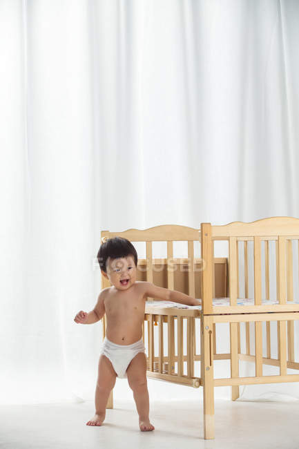 Повна довжина погляду порушеної азіатського малюка в підгузник спираючись на ліжечко і сміятися вдома — стокове фото