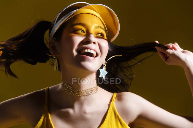 Attractive happy asian girl in transparent cap and star-shaped earrings smiling and looking away in studio — Stock Photo