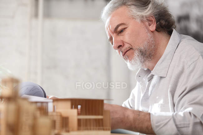 Professional focused mature architect working with blueprint and building model at workplace — Stock Photo