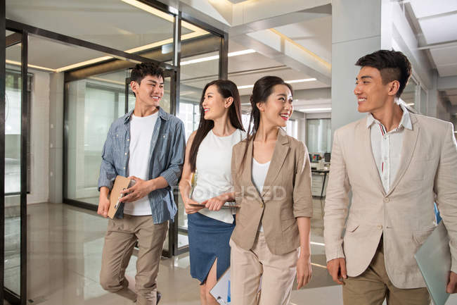 Smiling young asian businessmen and businesswomen talking and walking together in office — Stock Photo