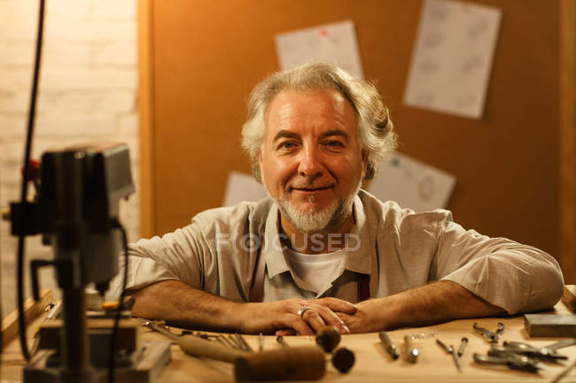 Happy mature male jewelry designer sitting at workplace and smiling at camera — Foto stock