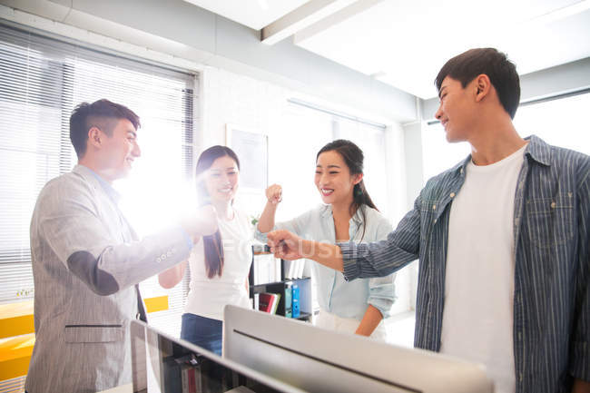 Glückliche junge professionelle asiatische Geschäftsleute stapeln Hände im Büro — Stockfoto