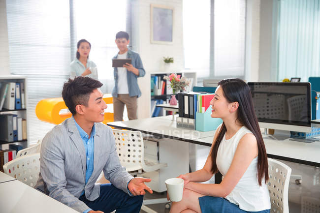 Smiling young business colleagues talking and looking at each other in modern office — Stock Photo