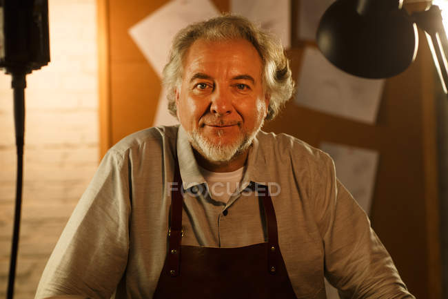 Happy mature male jewelry designer in apron smiling at camera in workshop — Foto stock