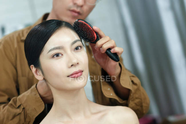 Cropped shot of man holding hairbrush and doing hairstyle beautiful young asian woman in beauty salon — Stock Photo