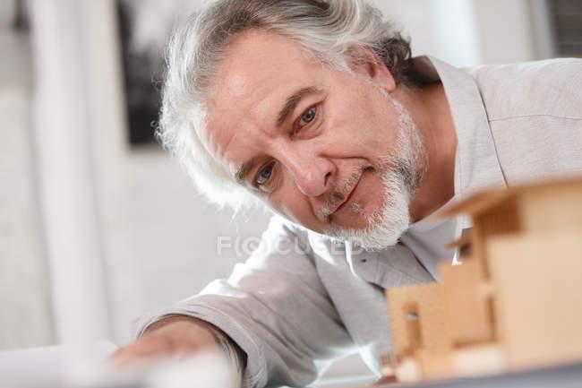 Architecte professionnel mature travaillant avec le modèle de construction sur le lieu de travail, objectif sélectif — Photo de stock