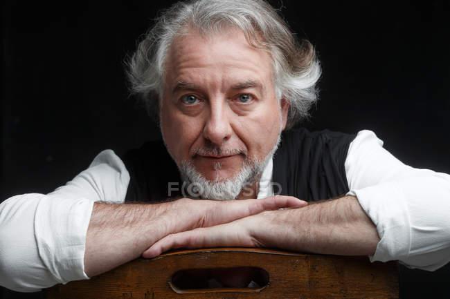 Porträt eines gutaussehenden grauhaarigen Mannes mittleren Alters, der auf einem Holzstuhl sitzt und isoliert auf schwarz in die Kamera blickt — Stockfoto