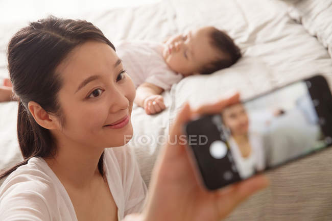 Happy young mother taking selfie with smartphone while baby sleeping on bed — Stock Photo