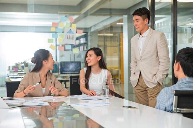 Усміхаючись молодих азіатських ділових колег обговорювали новий проект в офісі — стокове фото