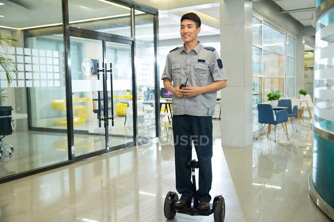 Lächelnder junger Sicherheitsmann fährt selbstbalancierenden Roller und hält Walkie-Talkie im Business Center — Stockfoto