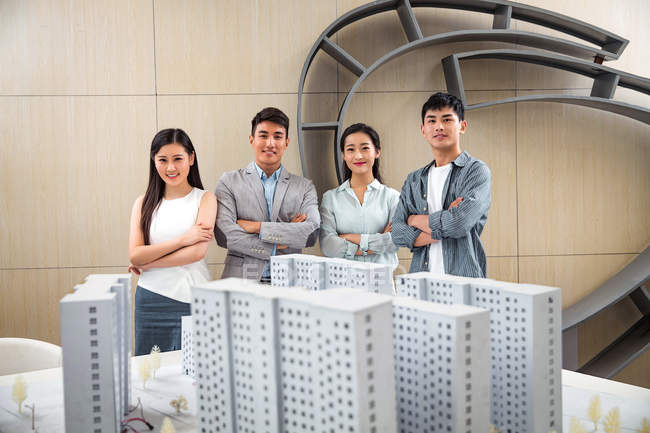 Team of professional confident young architects standing with crossed arms near project and smiling at camera in office — Stock Photo