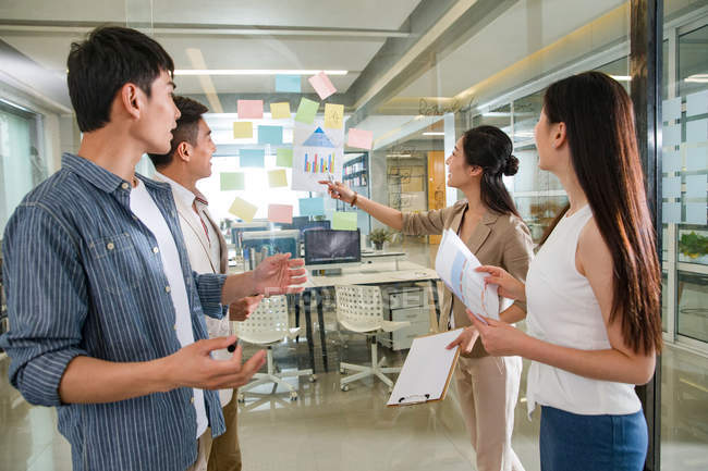 Smiling young professional asian businesspeople working with sticky notes in office — Stock Photo