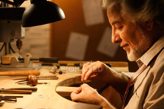 Side view of smiling mature male jewelry designer working with tools in workshop — Stock Photo