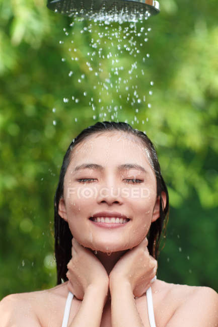 Attractive smiling young asian woman with closed eyes taking shower on green natural background — Stock Photo