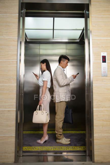 Vista laterale di giovane uomo d'affari e donna d'affari in piedi back to back e utilizzando smartphone in ascensore — Foto stock
