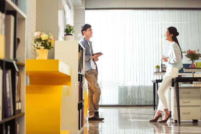 Side view of smiling male and female coworkers talking in modern office — Stock Photo