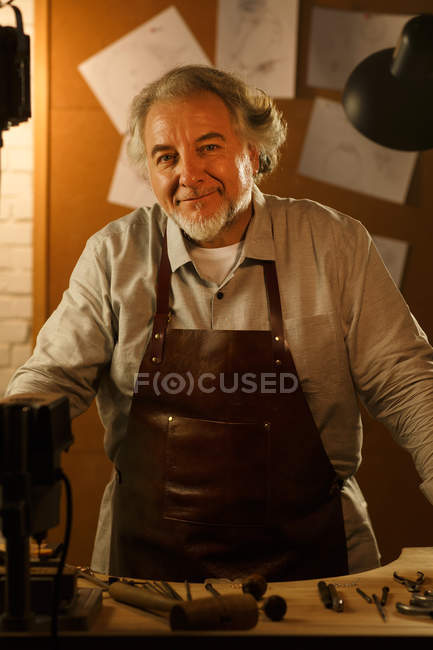 Happy mature jewelry designer in apron standing and smiling at camera in workshop — Foto stock
