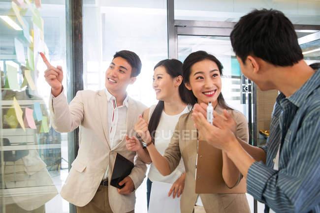 Souriant jeunes asiatiques collègues d'affaires discuter projet dans bureau moderne — Photo de stock