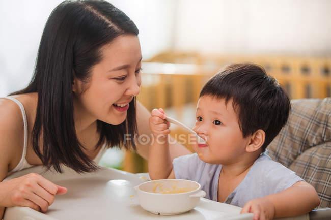 Glückliche junge asiatische Frau schaut auf niedliche kleine Kind mit Löffel und essen zu Hause — Stockfoto