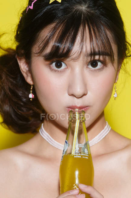 Beautiful young asian woman holding glass bottle with yellow drink and looking at camera in studio — Stock Photo