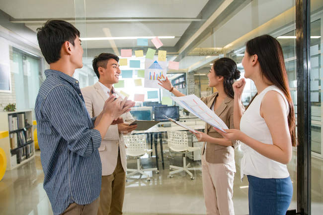 Side view of professional young asian businessmen and businesswomen standing together and working with papers in office — Stock Photo
