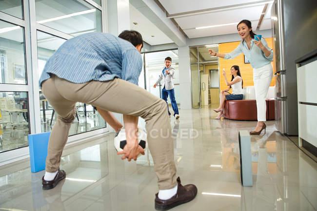 Giovani uomini d'affari asiatici e donne d'affari che giocano a calcio insieme in ufficio moderno — Foto stock