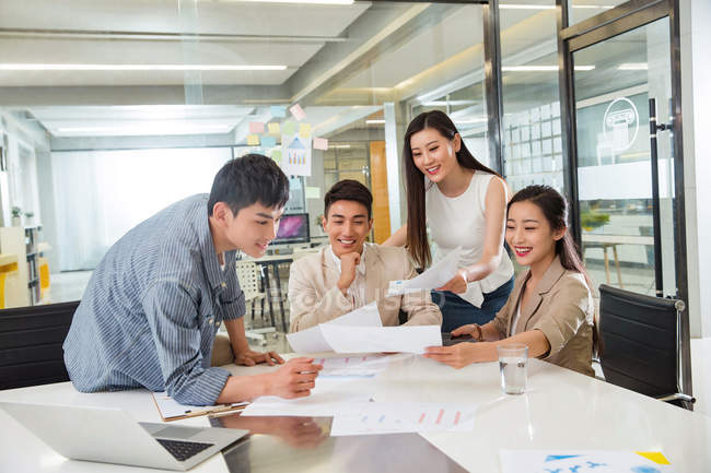 Smiling young asian businessmen and businesswomen working with papers in modern office — Stock Photo