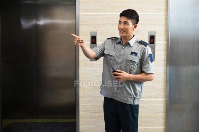 Улыбаясь молодых азиатских охранник проведения рации и указывая далеко возле лифтов — стоковое фото