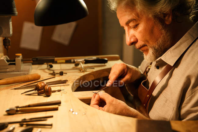 Profile of concentrated mature jewelry designer working with ring and tools in workshop — Foto stock