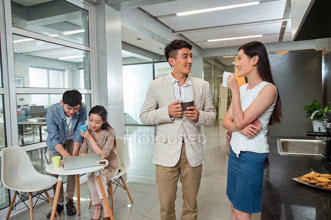 Happy young asian businessman and businesswoman drinking coffee while colleagues using laptop behind in office — Stock Photo