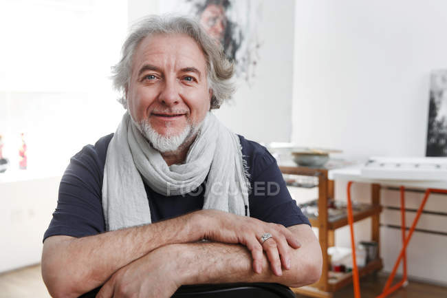 Schöner reifer männlicher Künstler sitzt auf Stuhl und lächelt in die Kamera im Studio — Stockfoto