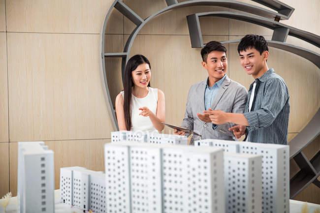 Профессиональные улыбающиеся Молодые архитекторы обсуждают проект в офисе — стоковое фото