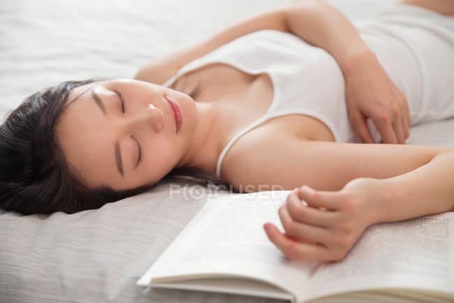 Красиві азіатські брюнетки Спляча з книгою на ліжку — стокове фото