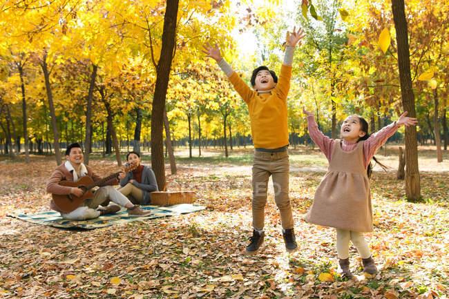 Bambini felici che giocano con le foglie autunnali mentre i genitori riposano sul plaid a scacchi nel parco — Foto stock